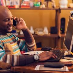 Content man uses cell phone at desk in home office