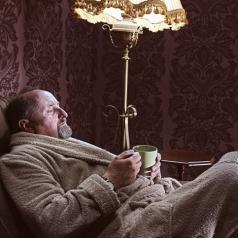 Man in robe sitting and drinking tea
