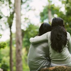 Rear view of hugging female friends sitting in the park