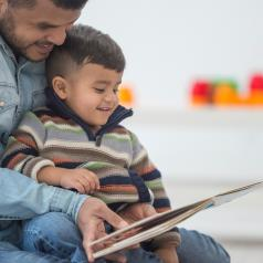Young child sits in lap of parent with short hair who reads large picture book. Both parent and child are smiling