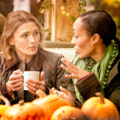 Two friends sit in cafe in front of display of pumpkins and drink coffee and have conversation