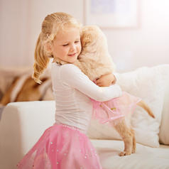 A child plays dress-up with her puppy