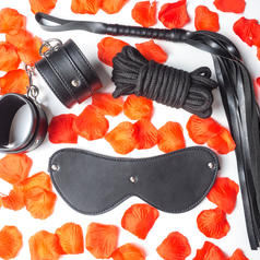 Photo of black leather handcuffs, blindfold, flogger, and rope on flower petal background