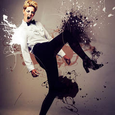 Tall person with short hair wearing bowtie, shirt, slacks, and heeled boots kicks out against splashes of paint