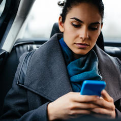 Upset person in business dress and scarf with ponytail texting in car as passenger