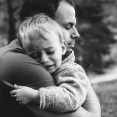 Little boy crying on father