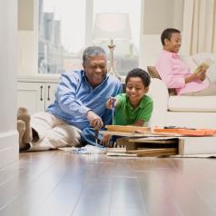 Child helps grandfather build furniture while child