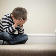 Child sits on stairs, covering face with both hands
