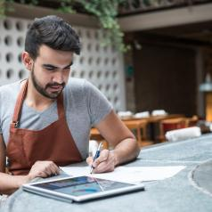 Young person with dark hair and business apron works at bar table on tablet