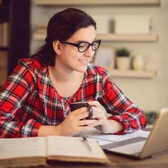 Young adult with long hair and glasses works at table with books and computer holding mug