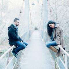 Young couple with relationship difficulties sitting on opposite sides of a bridge