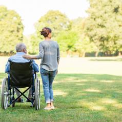 Rear view photo of caregiver with hair in bun standing next to person in wheelchair, hand on their shoulder