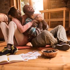 Laughing couple embraces at home, cards ant notebook and snacks next to them on floor