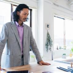 Person wearing casual suit stands in bright workspace looking at project on table with worried expression