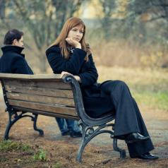 Two people sit on opposite sides of a bench on cold day, facing different directions