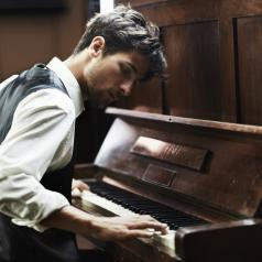Pianist with short hair wearing vest and dress shirt sits at piano intent on playing