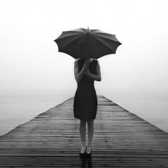 A woman in a black dress hides her face with her umbrella.