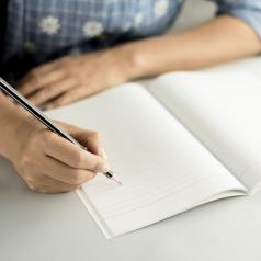A woman writes in a notebook with her pencil.