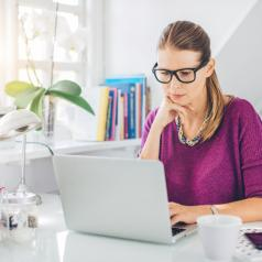 Person with glasses and serious expression works on computer in home office