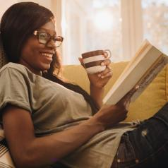 Person sitting on the sofa reads while drinking from brown and white mug