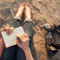 Photo of legs and feet of person who is holding a journal on lap and writing on sandy beach
