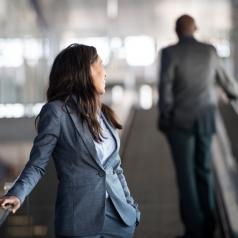 Person with long hair leans back on escalator rail looking at back of colleague in suit
