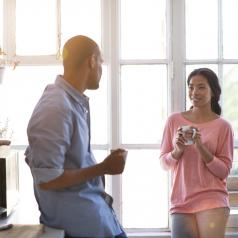 Two adults stand in the kitchen at home, holding mugs and talking with each other