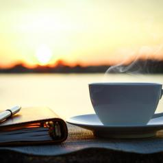 Coffee, journal, and pen on table outside at sunrise