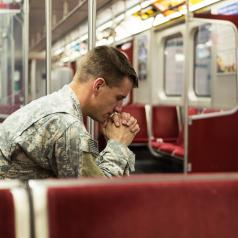A soldier sits in an empty train car, looking deep in thought.