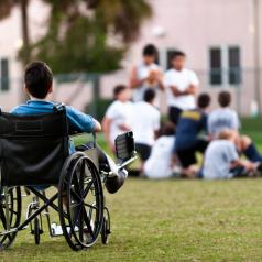 A 12-year-old child sitting in a wheel chair watching other kids getting together in the park while he is left behind.