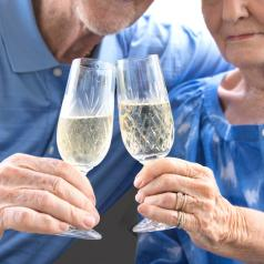 Close-up of an aged couple holding champagne flutes. They are both wearing blue shirts.