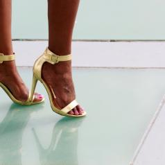 A woman with golden high heels stands atop a green tile floor.