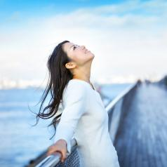A young woman leans against a railing, smiling at the sky. One can see an out-of-focus ocean and pier behind her.
