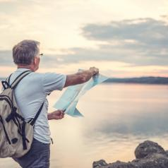 A middle-aged man walks along the coast with a map in his hands.