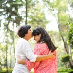 Latin mother kissing daughter with long hair on forehead in sunny, tree-lit area