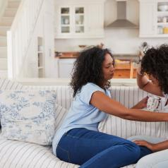 Mother talking to upset daughter on sofa in living room