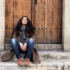 Person with long hair sits on stairs outside old wooden door, looking up with disappointed expression