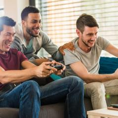Three men play a video game in a sunny room.