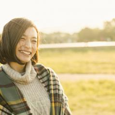 Person with short hair wearing sweater and shawl standing in field and smiling
