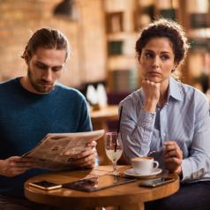 Pensive person with long curly hair sits in a cafe while partner looks down and away, reading newspaper.