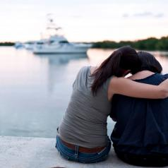 Rear view of two women sitting on pier embracing.