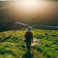Rear view of young adult in jacket walking along grassy hills with sun above ahead