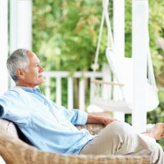 Relaxed older adult with short gray hair sits on porch, leaning back, with eyes closed