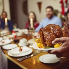 Closeup shot of a turkey being served during a feast at a dining table