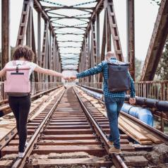 Couple holding hands over train track on bridge while walking together