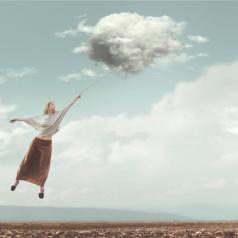 Person with long skirt flies through sky carried by cloud in dreamlike image