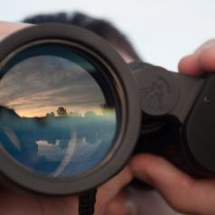 A reflection of the sky appears in a pair of binoculars held by an unseen man.
