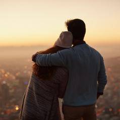 Rear view of couple standing on hillside looking out over city