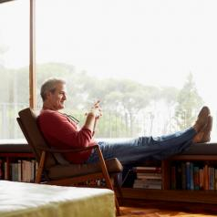 Side view of older adult relaxing with feet up, looking out large window
