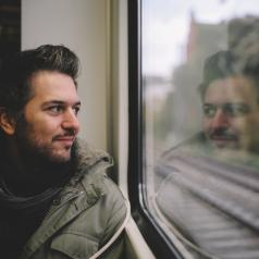 Adult with short hair and facial hair looks out window thoughtfully, smiling slightly